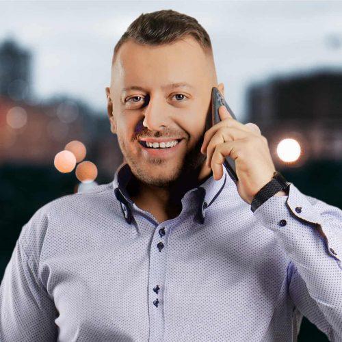 Portret, realitny makler v svetlomodrej koseli s telefonom pri uchu - Gabriel Slavkovsky